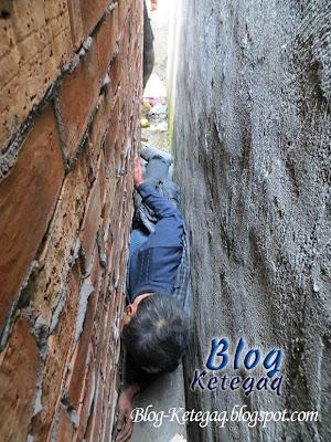 Lelaki cina tersangkut di lorong sempit antara dua rumah