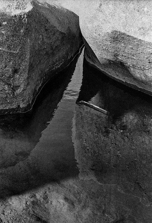 Pormenor de um reflexo de duas rochas nas águas de um pequeno lago de água junto à praia