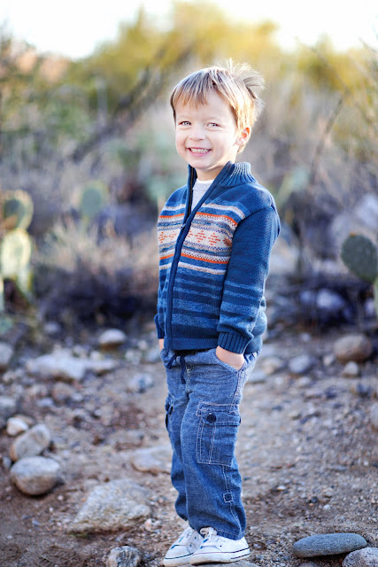 Little boy stands with hands in pocket in the desert