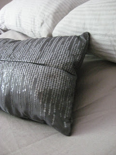 detail image of dark grey sequined pillow against pale grey bedding