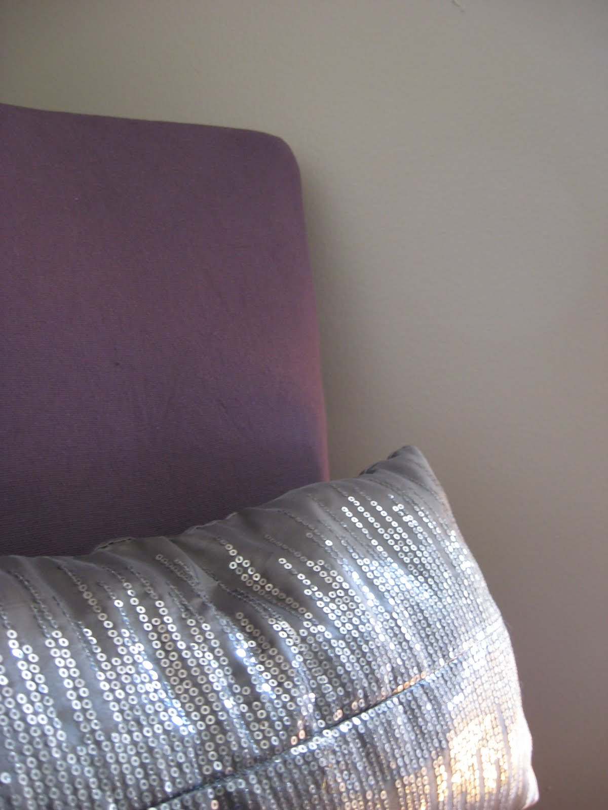 close up detail picture of purple reupholstered chair and grey sequined pillow