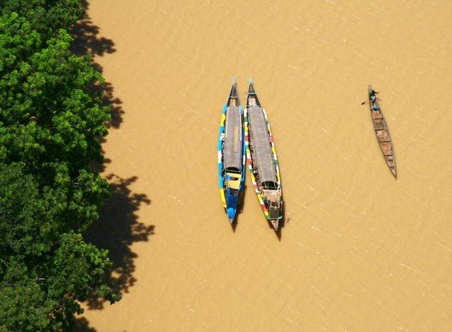 Vista aérea  vertical de dos pinazas para viajes y otra de  un pescador