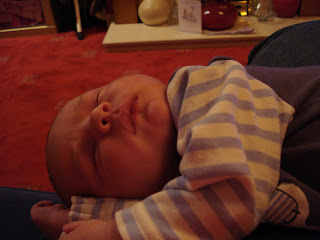 Baby Boy asleep on his side on Mummy's knee