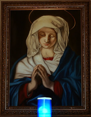 Picture of painting The Virgin in Prayer lit by candel light.
