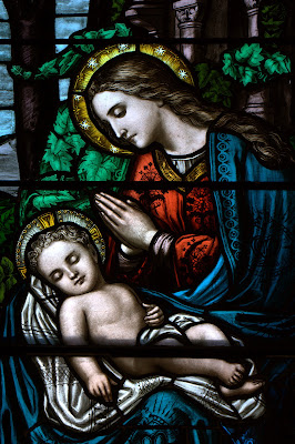 Stained glass window of praying Mary with baby Jesus