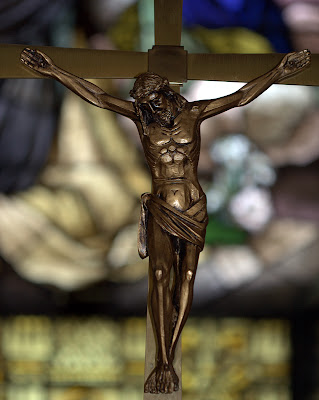 Bronze crucifix with stained glass window in the background