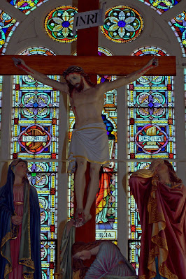 Picture of Crucifixion in balcony of church with large stained glass window in the backgroud