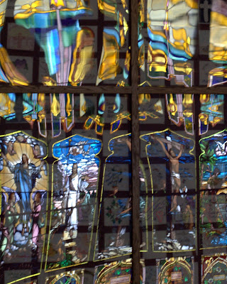 Reflections of Christ in stained glass windows reflected in glass of display case on opposite wall