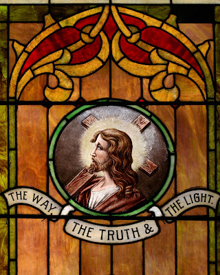 Stained glass window portrait of Christ with cross on shoulders with banner The Way, The Truth, and The Light