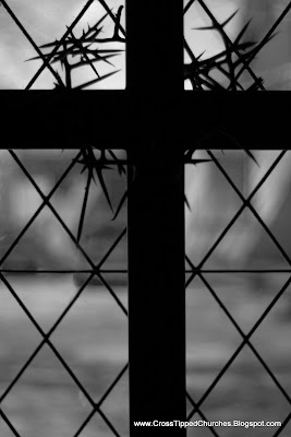 Black and white picture of silhouette of Cross with crown of thorns back lit with a diamonded patterned window.