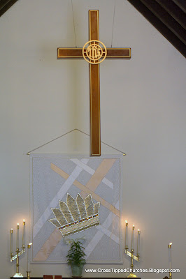 Back of altar with candles, suspended cross and hanging tapestry with crown.