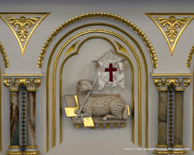 Relief on white alter with gold leaf of the resurrected Lamb of God.
