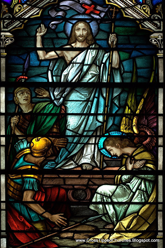 Stained glass window of the resurrected Christ outside the tomb with angel and soldiers.