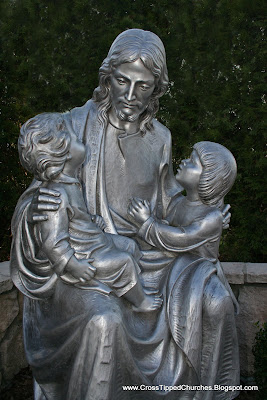 Day picture of large gray statue of Jesus holding children.