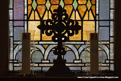 Two candles and a cross arranged in front of a stained glass window.