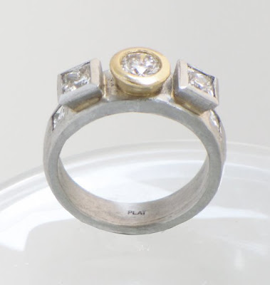 custom platinum engagement ring with diamonds in a yellow gold bezel