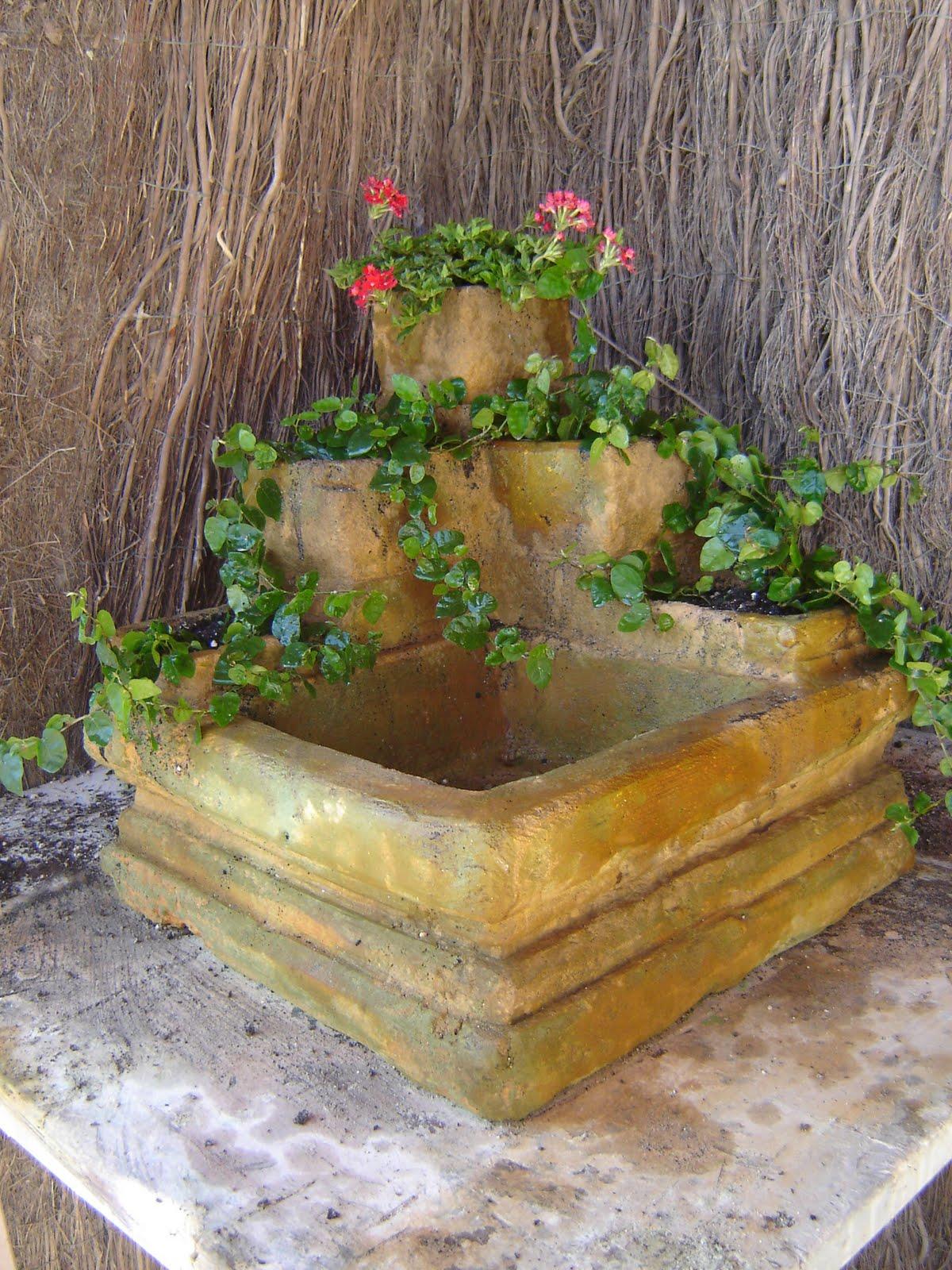 fuente de piedra con jardineras