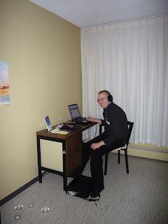 Miika istuu tietokoneella kuulokkeet päässä - aivan kuten Suomessakin!