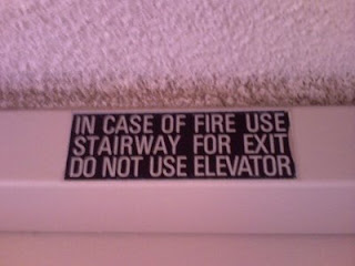 Sign above elevator reads 'In case of fire use stairway for exit do not use elevator' and lacks any punctuation