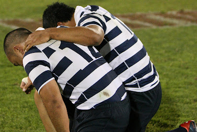 Centers Tupu Folau and Paul Lasike take a knee, sobered by the victory