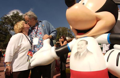 ©Disney - Russi Taylor and Wayne Allwine, the voices of Minnie Mouse and Mickey Mouse respectively, share a kiss near the InspEARations statue they designed to help celebrate Mickey and Minnie's 75th Birthday.
