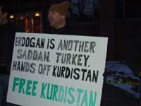 Protestor with sign reading, 'Erdogan is another Saddam. Turkey, hands off Kurdistan. Free Kurdistan' [Credit: Leyla Zana]