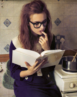 Hipster girl reading book at work.