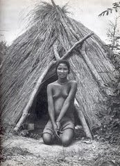 Rapariga Bochimane sentada frente à choca