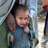A child is held by an anti-Taliban solider December 14, 2001 on the road to front lines near the Tora Bora area of Afghanistan. Clouds of smoke from U.S.-led bombing billow over Al-Qaeda positions as American and anti-Taliban forces continue to try to dislodge troops loyal to Osama bin Laden from the mountainside.