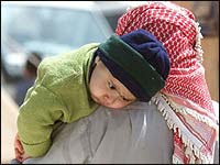 An Iraqi refugee carries his son at a refugee camp near the far eastern Jordanian town of Ruweished, March 29, 2003. [NPR - Corbis]