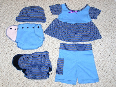 picture of 2 diapers with a matching dress, shorts, and a hat