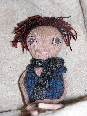 knitted doll wearing scarf and vest