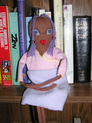 doll sitting on bookshelf in pink and lavender dress