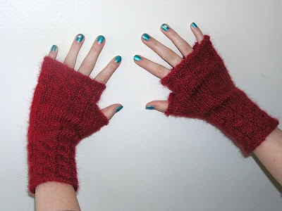 two hands with blue nailpolish and red fingerless gloves on a white wall