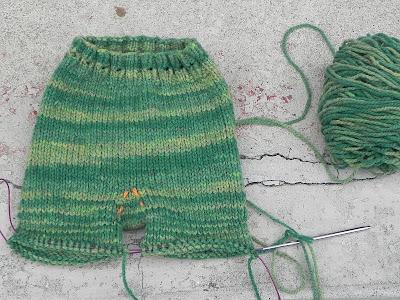 a pair of green wool longies in progress, still on the knitting needles