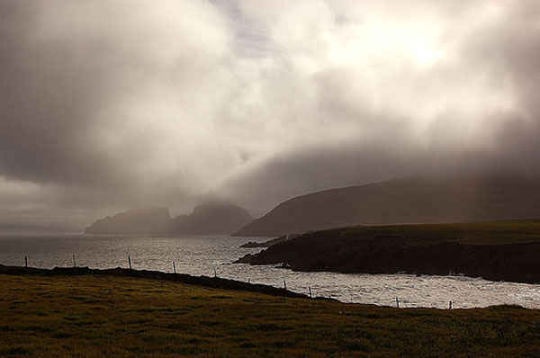 Vun St. Finian's Bay aus, d'Puffin Island am Hannergrond
