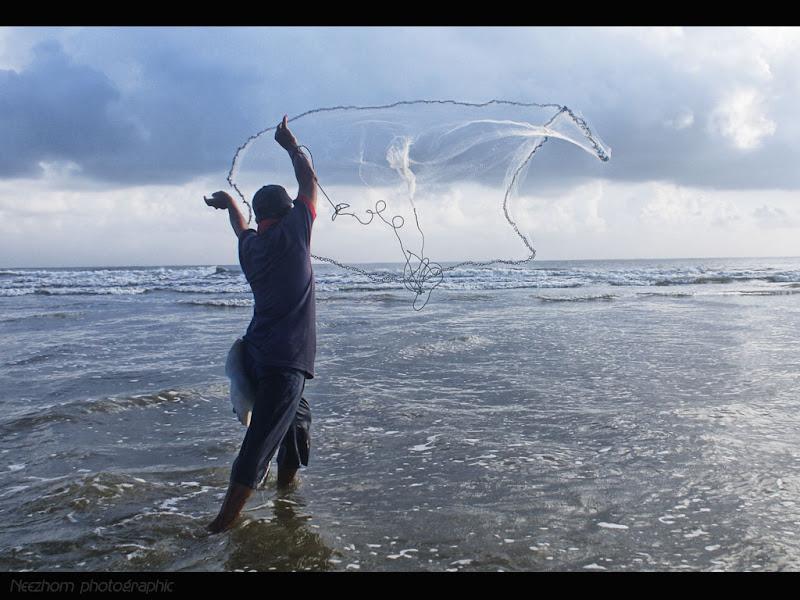 orang menebar jala di tepi pantai Kuala Ibai