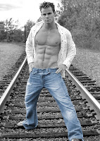 muscular guy on railway tracks in blue jeans
