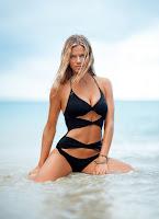 Блондинка с мокрыми волосами Бруклин Деккер в черном купальнике сидит в волнах моря