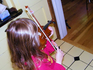 Curly with cars stickers on either end of her violin bow