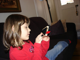 Sister Curly Miss plays games on Mommy's iPod, stretching her long legs along the couch.