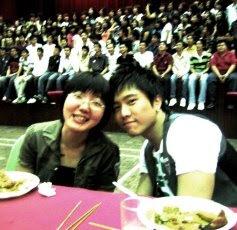 我和鱼丸。背景是在学校礼堂舞台上壮观的百人大合照。