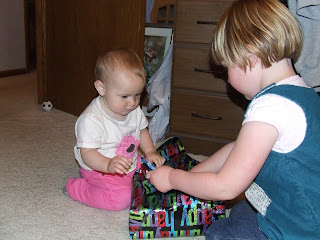 Harmony helping Sierra open her first (early) 1st birthday present from Auntie Tania