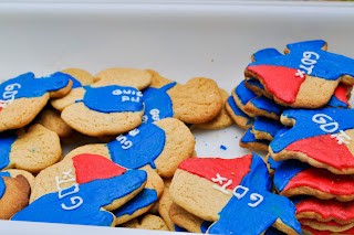 Sugar cookies in the shape of Texas with red white and blue icing, they say GDTX on them. There are also puppy shaped cookies with little blue jackets that begin to say Guide Dog Puppy. You can see G.U.I. and P.U.