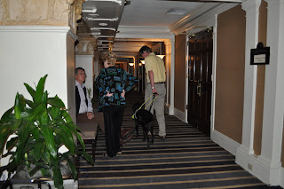 This is a picture looking down the hallway of the hotel where the fundraiser was, it is a picture of one of the GDTX employees Ernie and his black lab guide dog