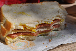 Close up of Darrell's sandwich its half eaten and has mustard all over it