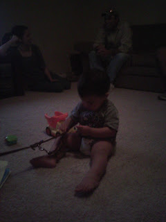 Picture of the baby with his toys surrounding him, he is holding the handle section of Bob's leash.