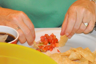 close up of a woman's hands, she is using two chips to get her salsa onto one of them