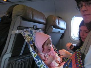 baby in a flyebaby seat on an airplane. traveling with a baby on an airplane
