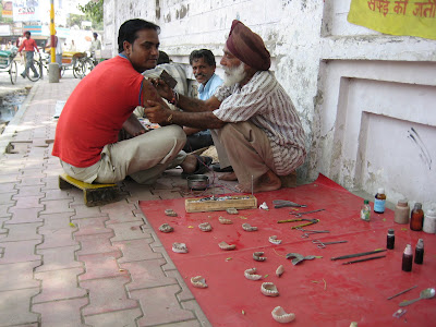A man giving tattoos on the street corner next to a man making dentures.